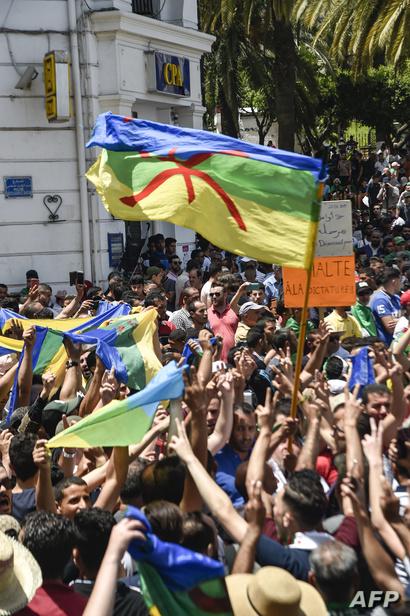 """نشطاء يرفعون العلم الأمازيغي خلال إحدى مسيرات """"حراك الجزائر"""""""