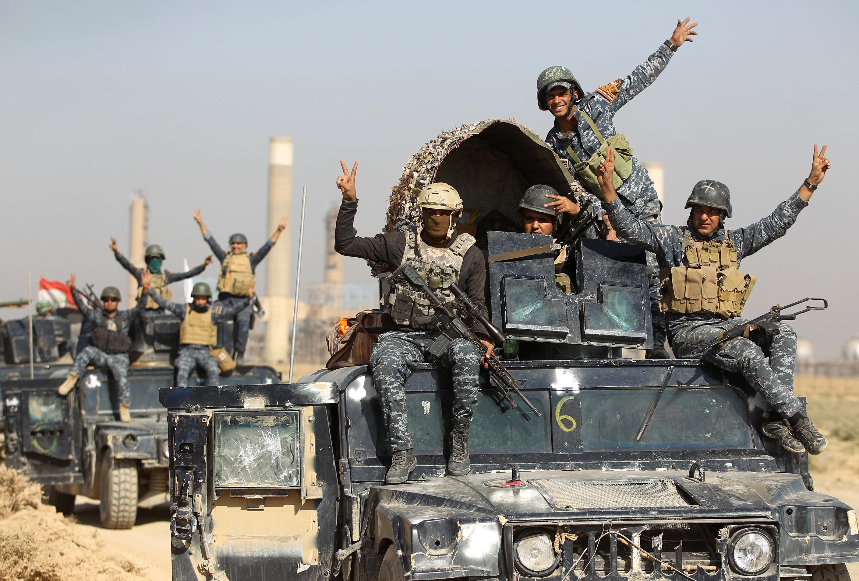 أفراد من القوات العراقية يرفعون علامة النصر أمام إحدى منشآت النفط في كركوك