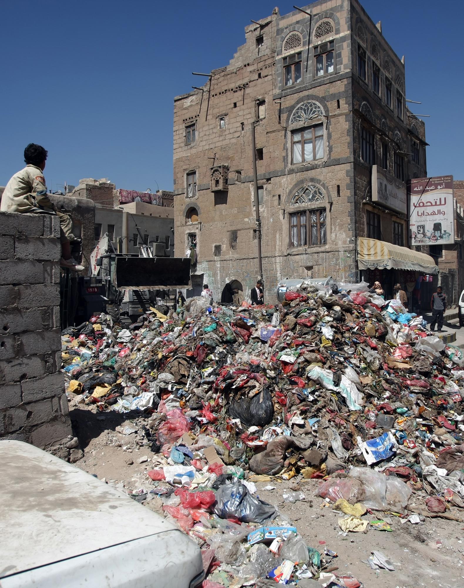 طفل يمني يستند إلى حائط قرب نفايات في شارع صنعاء