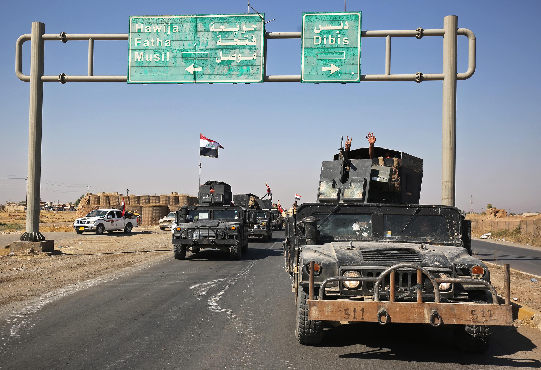 آليات عسكرية عراقية تسير في أحد الشوارع المؤدية إلى كركوك وتظهر شاخصة تشير إلى مدينة دبس التابعة لمحافظة كركوك