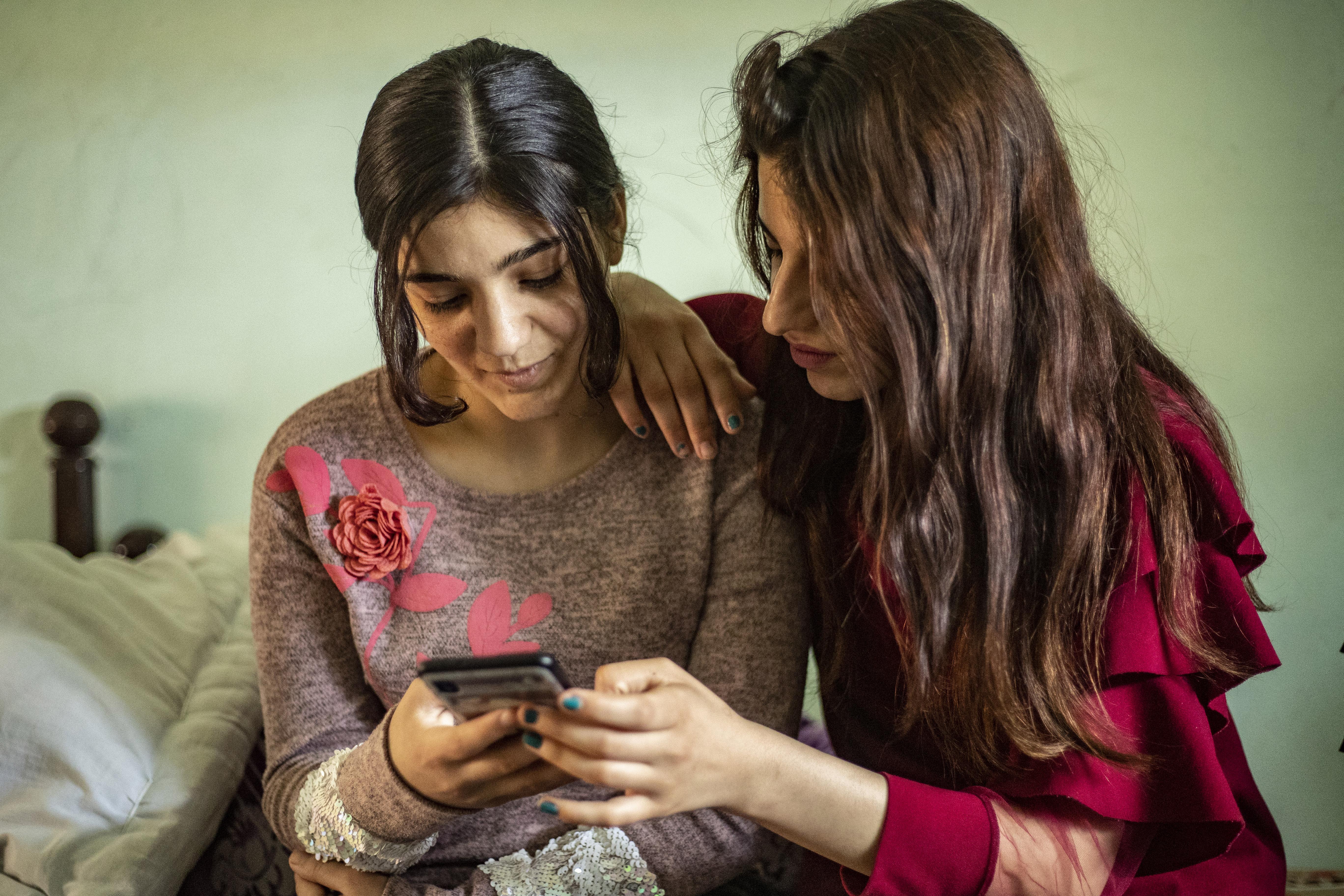 الشابة الأيزيدية ليلى عيدو (يسارا) تنظر إلى الصور مع صديقة لها في ريف الحسكة شمال شرق سوريا
