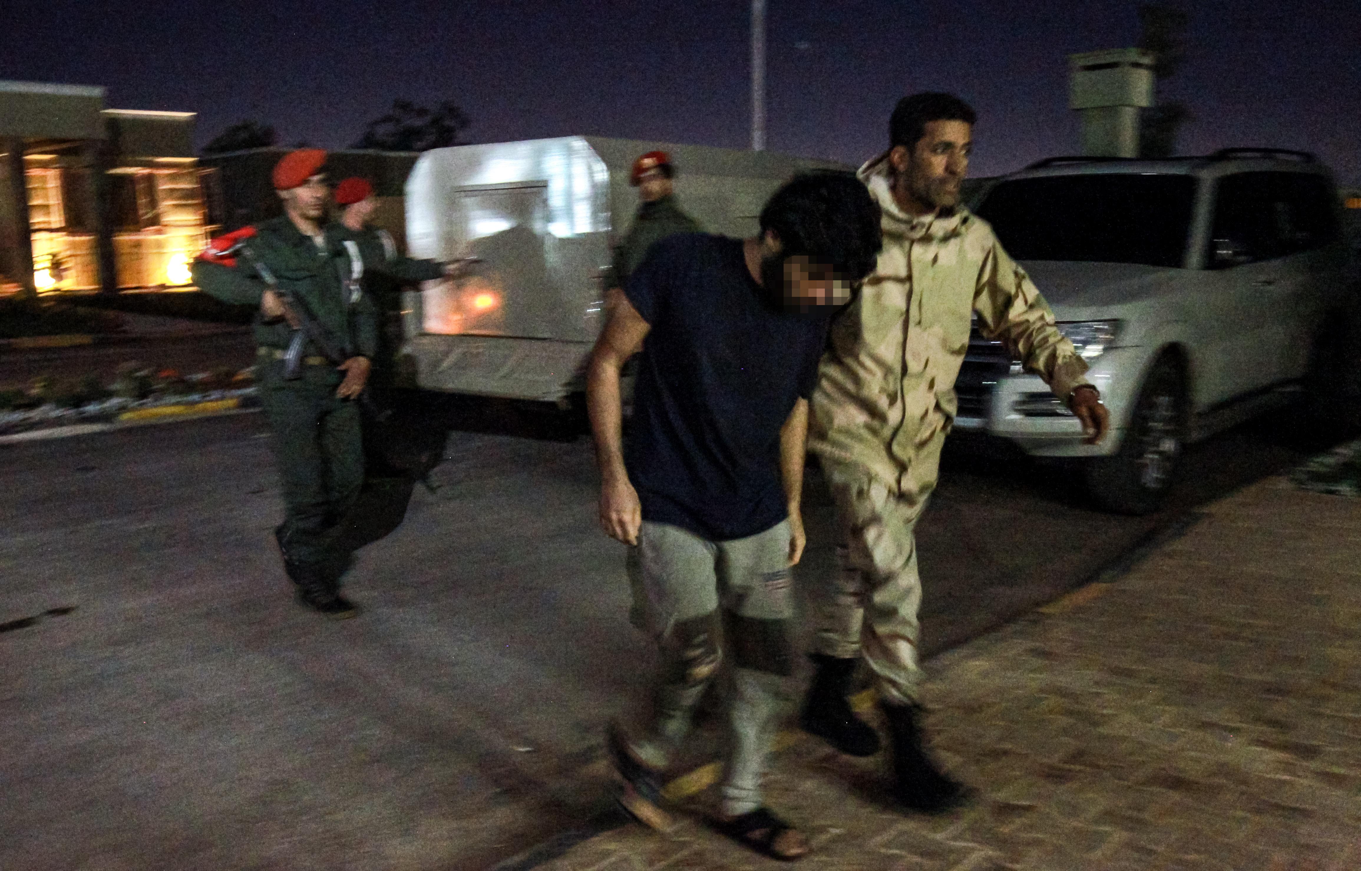 جندي من قوات حفتر يرافق سجينًا سوريا أسرته قوات حفتر أثناء هجومها بالقرب من العاصمة طرابلس