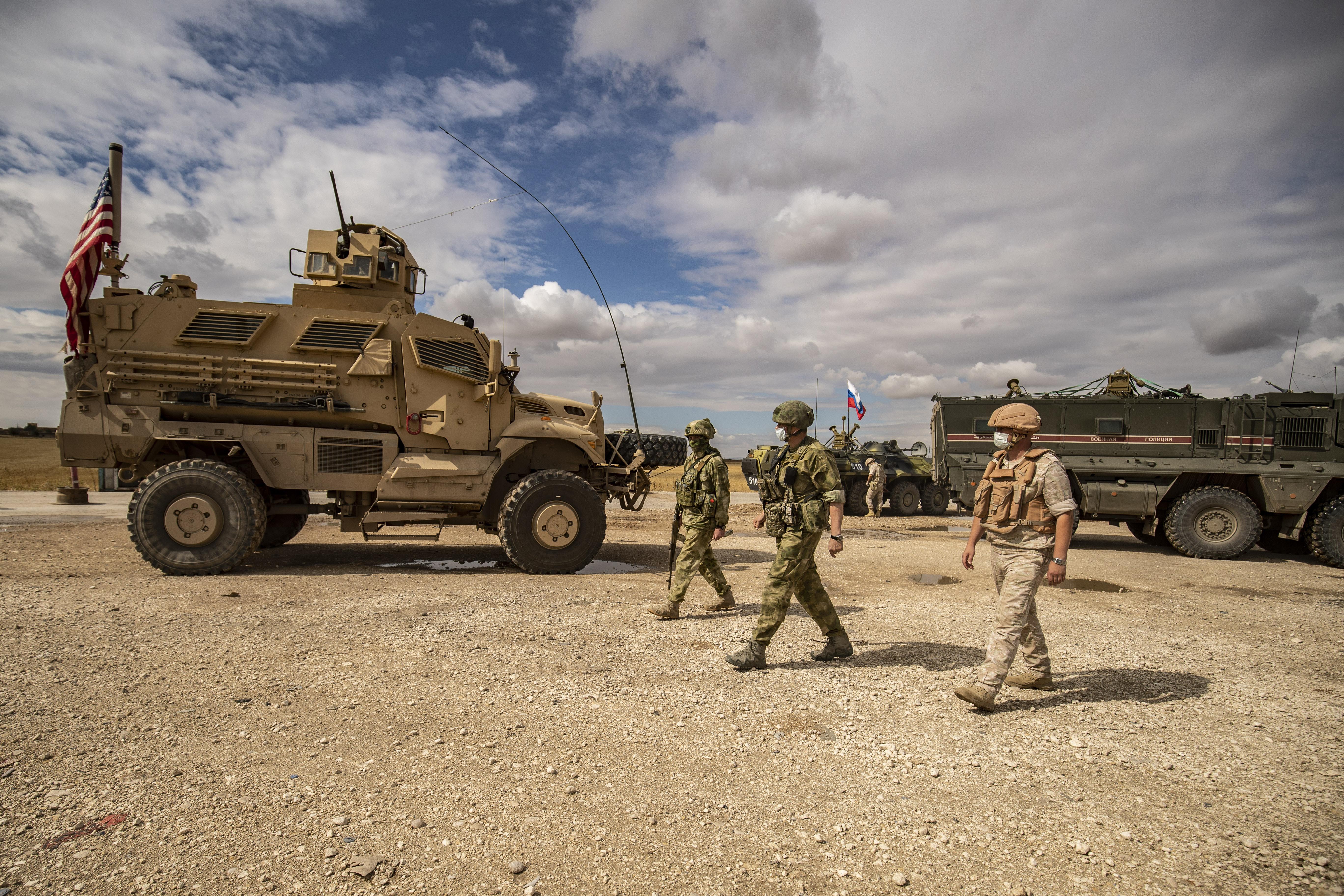 جنود روس يمشون أمام مركبة عسكرية أمريكية على الطريق السريع M4 بالقرب من بلدة تل تمر في سوريا