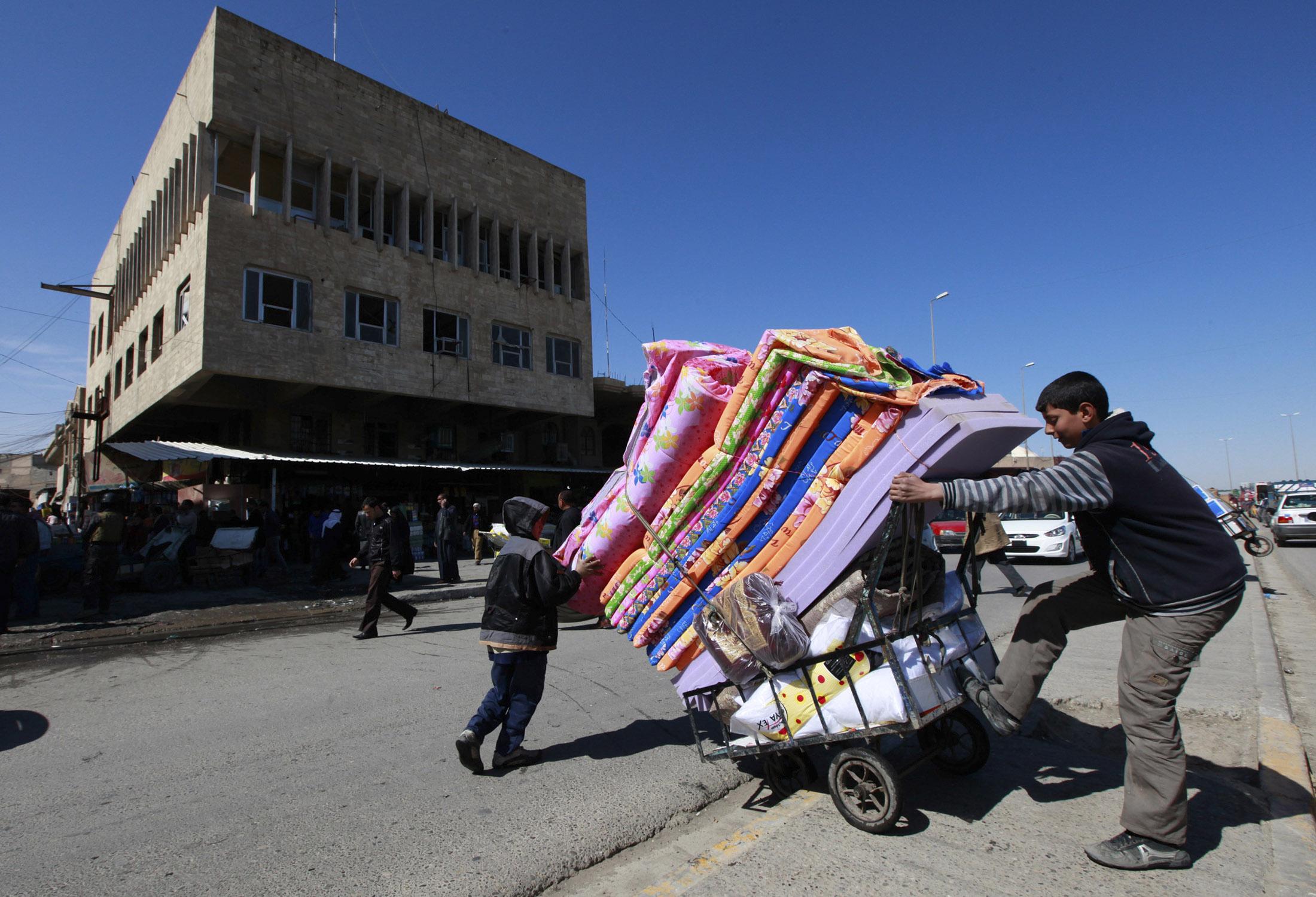 شاب عراقي ينقل أغراضا بواسطة عربة في أحد أسواق الموصل