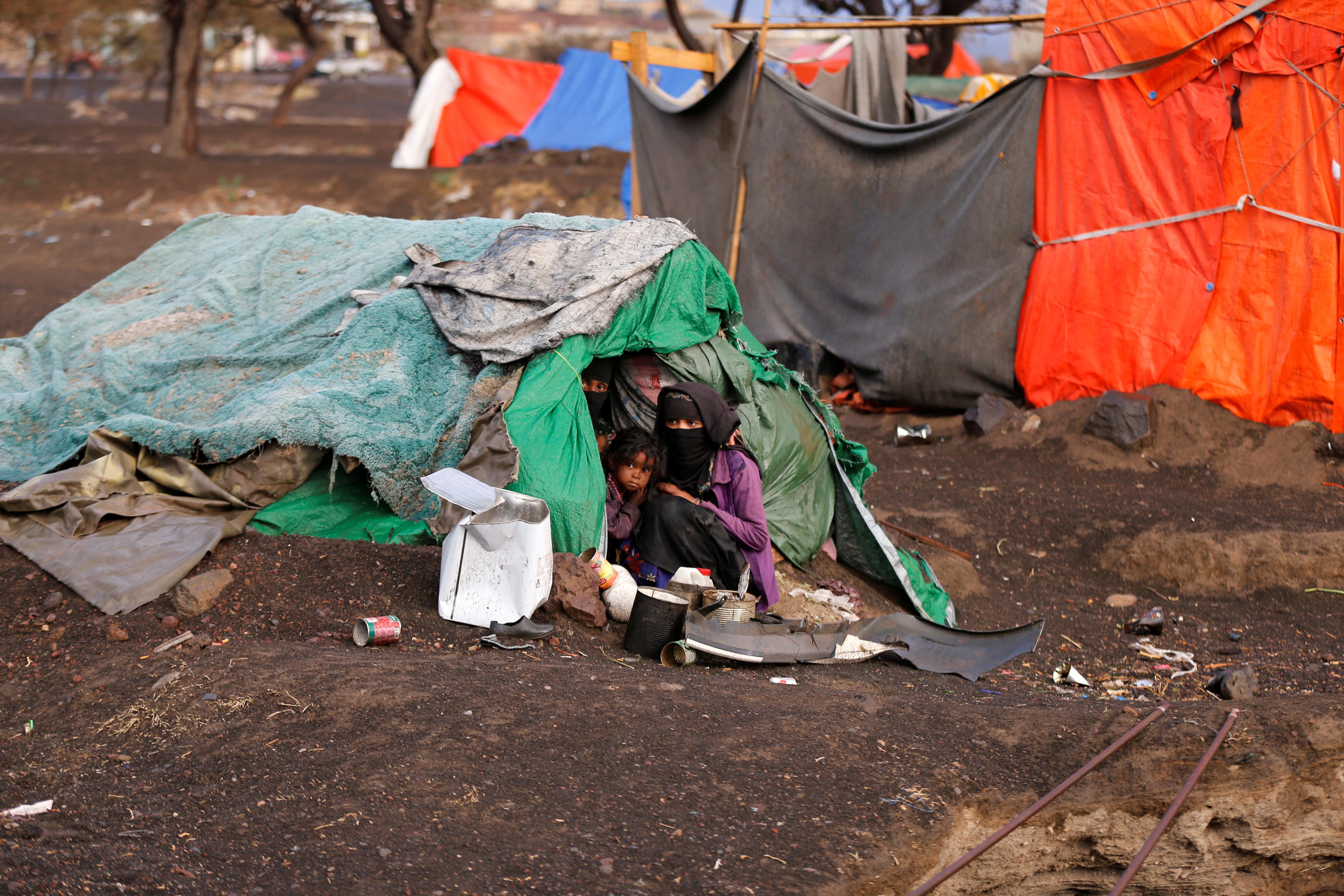 امرأة يمنية وأطفالها يجلسون في خيمتهم بمخيم للنازحين بالقرب من العاصمة صنعاء