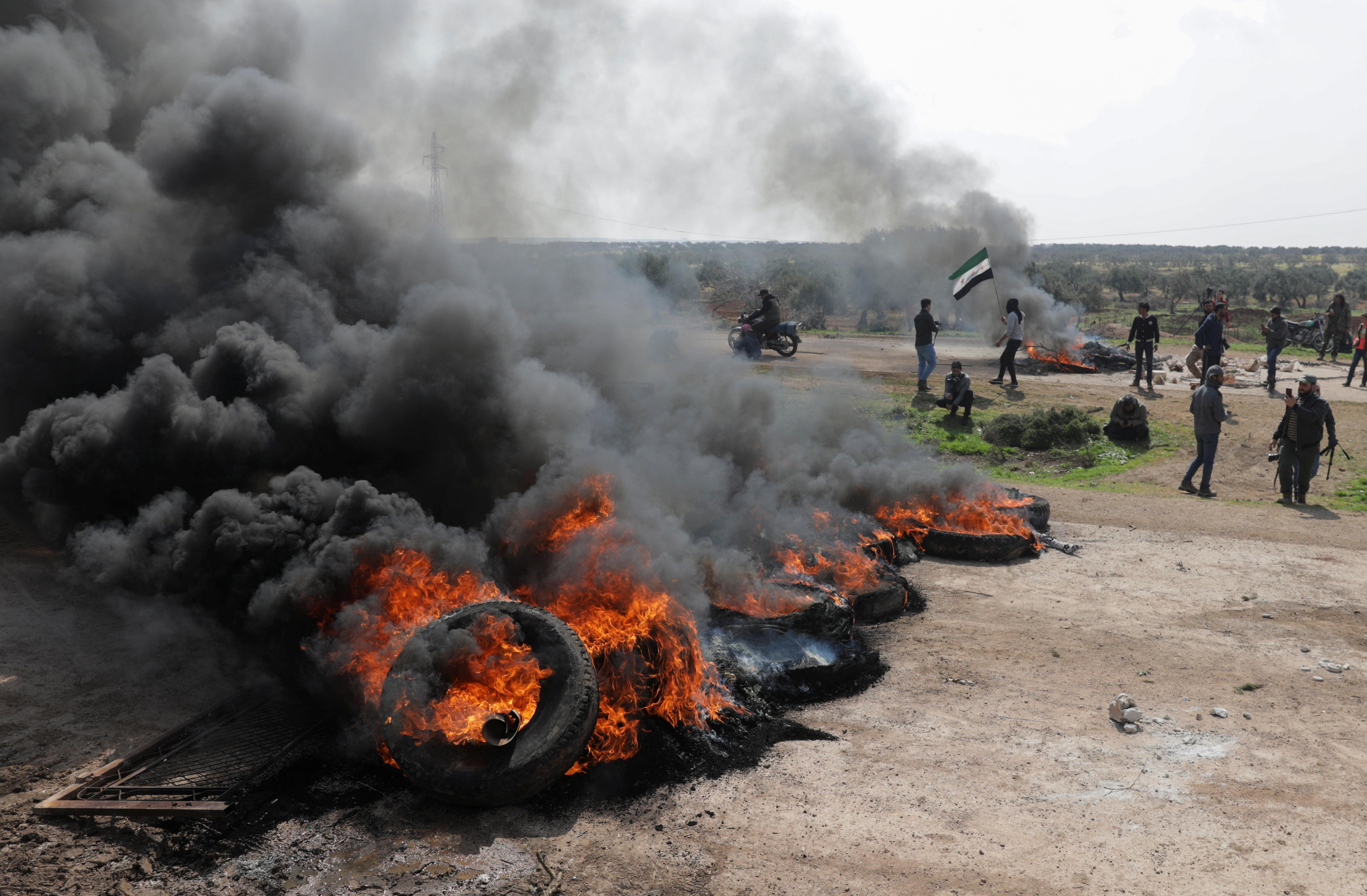 حرق إطارات خلال الاحتجاج على اتفاقية الدوريات الروسية والتركية المشتركة على الطريق السريع M4 في محافظة إدلب بسوريا