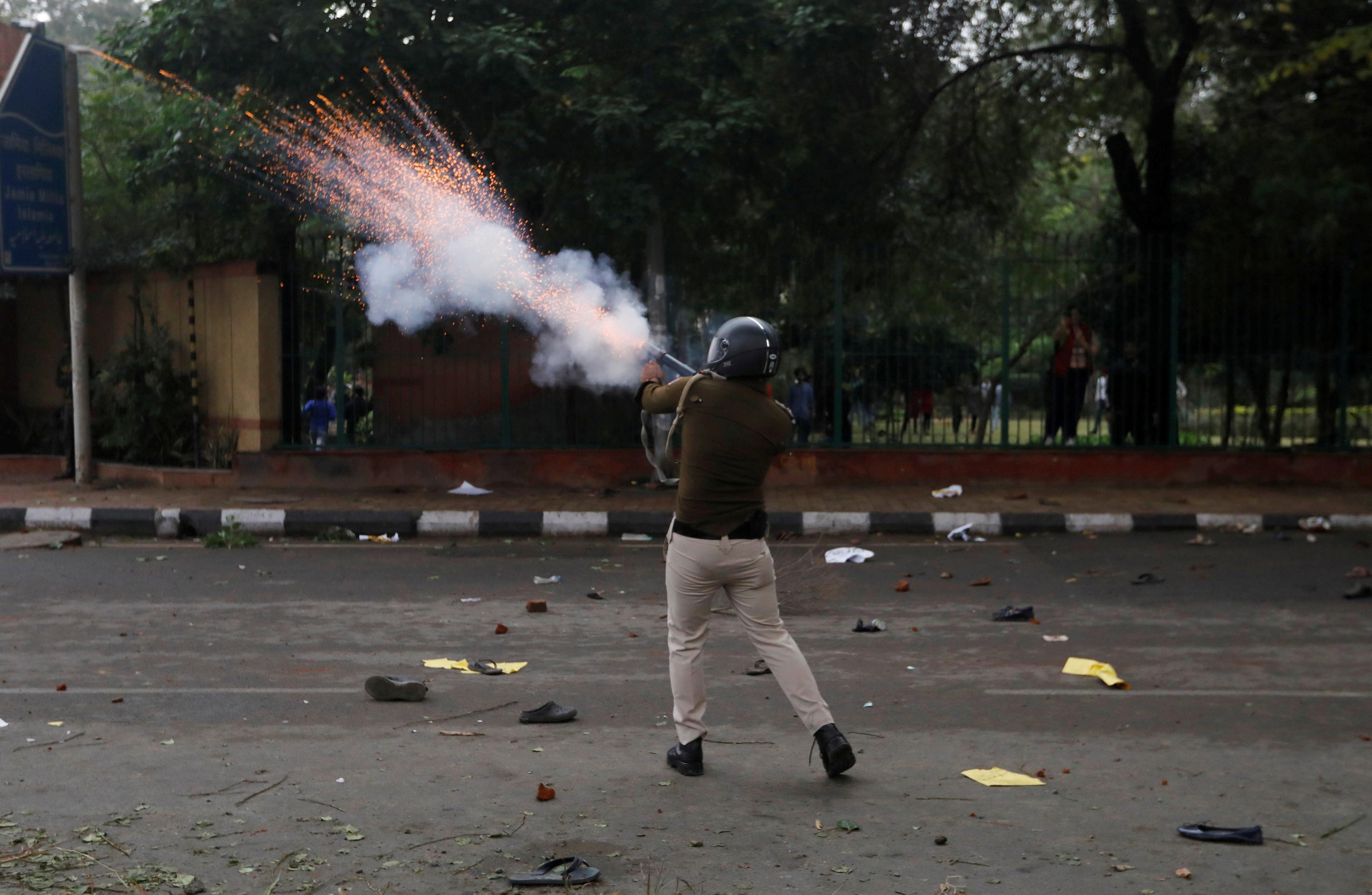 شرطي مكافحة الشغب يلقي بقنابل الغاز المسيل للدموع صوب المتظاهرين في العاصمة نيودلهي