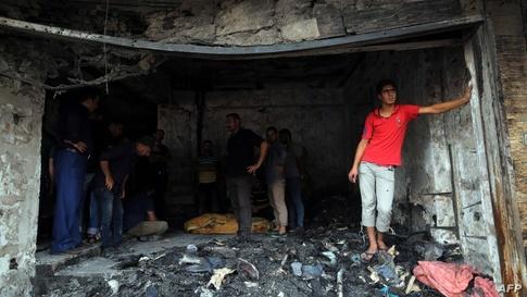 أحد أصحاب المحال في منطقة الكرادة يقف داخل محله المتضرر جراء تفجير إرهابي/وكالة الصحافة الفرنسية