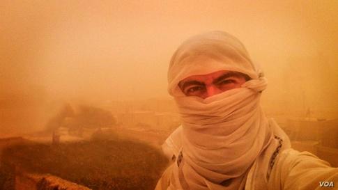 يظهر توغرال في الصورة مغطيا معظم وجهه أثناء عاصفة رملية في الرقة، عاصمة داعش المزعومة، في سورية، 6 كانون الأول/ديسمبر 2015