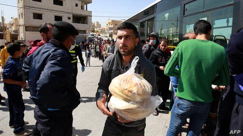 أردنيون يصطفون عند حافلة لبيع الخبز المدعوم من الحكومة في العاصمة عمان