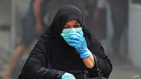 An Iraqi woman wearing protective gloves and mask walks by on a street in the Washash district, in western Baghdad, on April 6,…