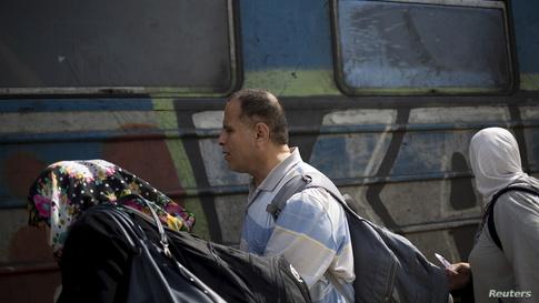 لاجئ مكفوف تساعده إحدى أقاربه في صعود القطار