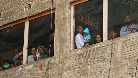 لاجئون سوريون ينظرون من نوافذ مبنى قيد الإنشاء يستخدمونه كمأوى في مدينة صيدا جنوب لبنان