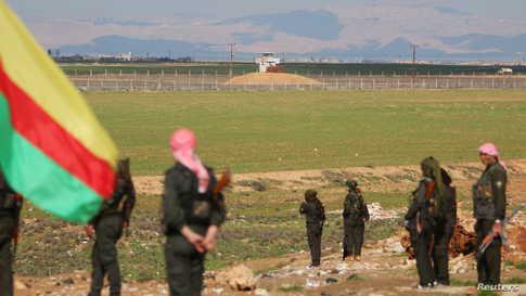 مقاتلون سوريون أكراد يقفون على الحدود السورية التركية