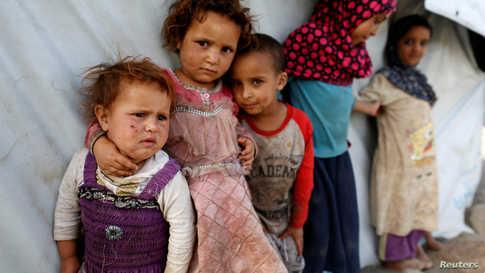أطفال يمنيون يقفون بجوار خيمة في مخيم للنازحين بالقرب من العاصمة اليمنية صنعاء