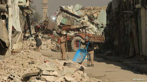 عمال نظافة يرفعون الأنقاض من احد شوارع المدينة القديمة في أيمن الموصل شمال العراق