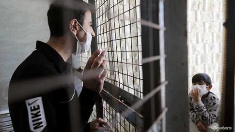 رجل سوري يتحدث إلى أسرته عبر سور في مركز للحجر الصحي في جسر الشغوربمحافظة إدلب