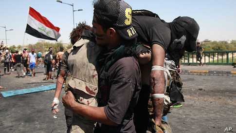 An injured anti-government protester is rushed to a hospital during clashes in Baghdad, Iraq, Sunday, May 10, 2020. Protesters…