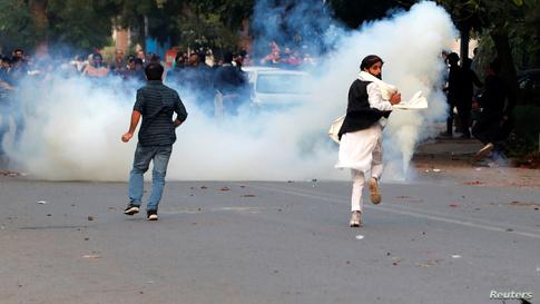 متظاهر يفر ليقي نفسه من الغازات المسيلة للدموع في تظاهرة ضد تعديل قانون الجنسية في العاصمة نيودلهي.