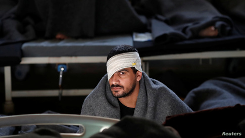 A foreign prisoner with a bandage wrapped around his head, suspected of being part of the Islamic State, sits inside a prison…