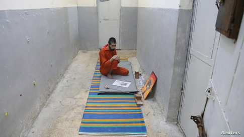Abed El-Hamed Atiya, an Iraqi prisoner, suspected of being part of the Islamic State, sits next to a picture he drew inside a…