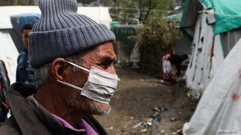 A migrant wears a protective face mask at a makeshift camp for refugees and migrants next to the Moria camp, during a…