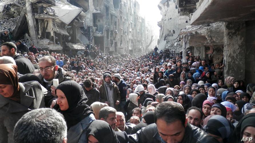 صورة لآلاف اللاجئين في مخيم اليرموك ينتظرون دورهم للاستفادة من المساعدات الإنسانية