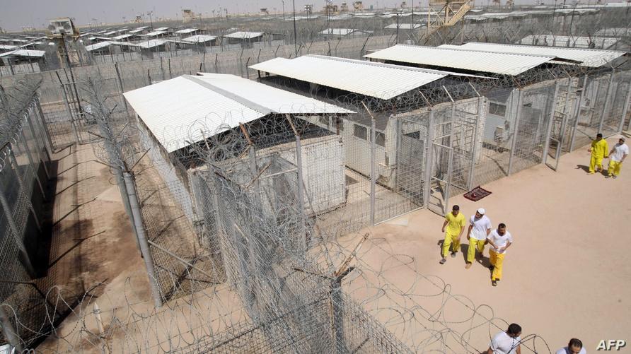 سجناء متشددون يمشون في الملعب الرياضي بسجن بوكا
