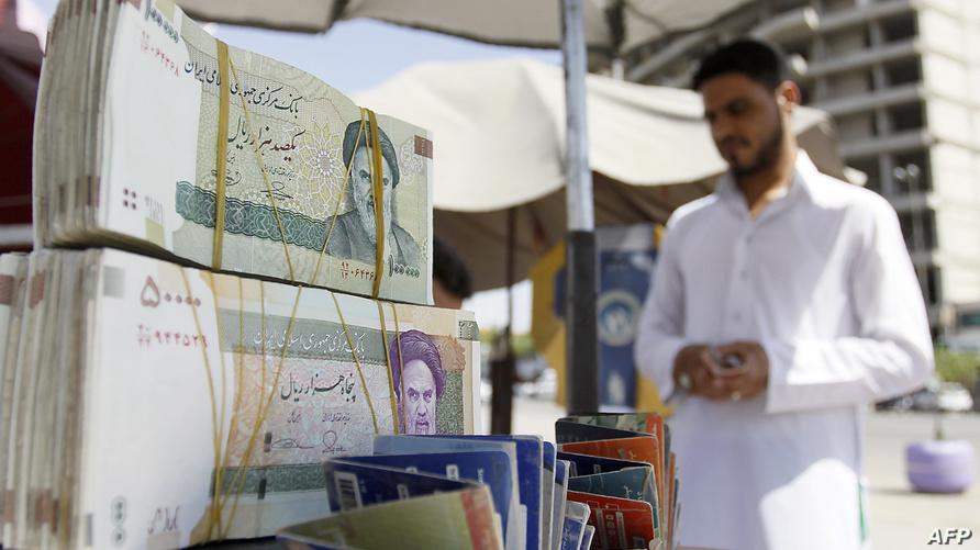 صرّاف عراقي يبيع العملة الإيرانية في أحد شوارع مدينة النجف
