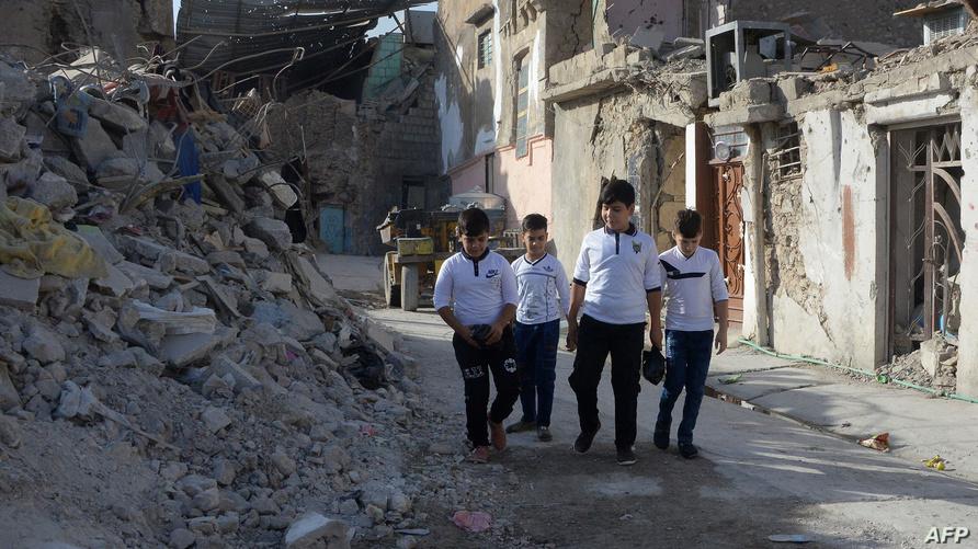 أطفال عراقيون يسيرون في حي ضيق من أحياء الموصل تحيطهم المنازل المهدمة في طريقهم إلى المدرسة