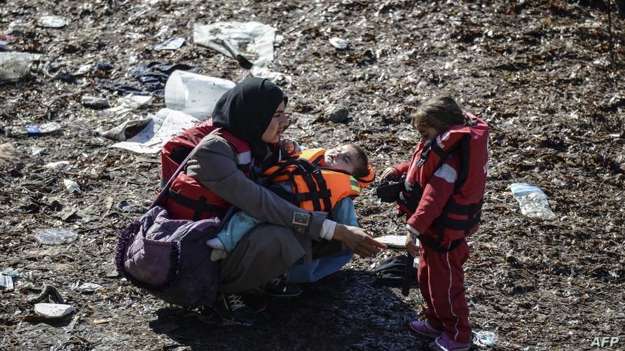 صورة أرشيفية: لاجئة سورية تحاول مع عائلتها الهجرة إلى اليونان من تركيا