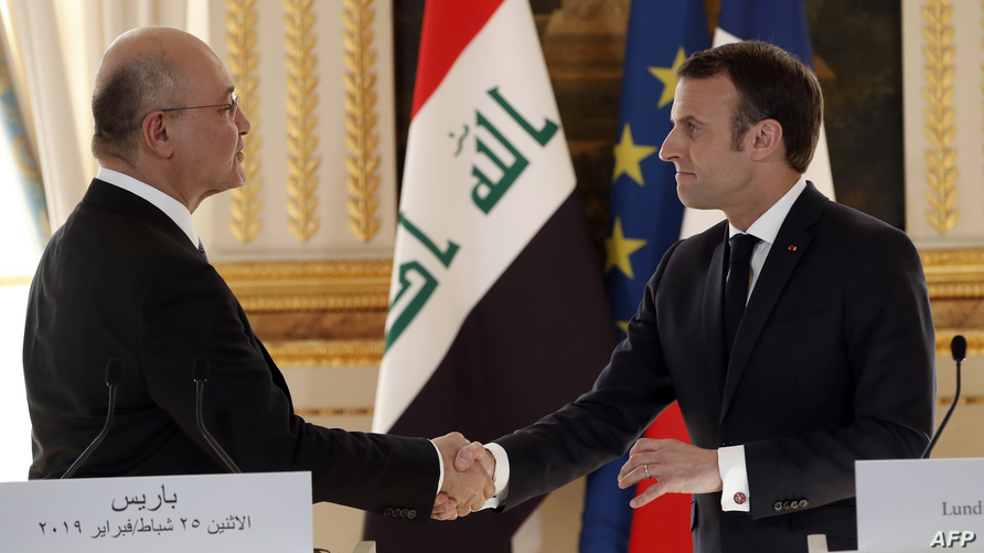 الرئيس الفرنسي يصافح الرئيس العراقي أثناء حضوره مؤتمرًا صحفيًا في قصر الإليزيه في باريس