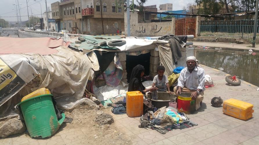 اليمني سعيد سالم يجلس بجوار زوجته أمام خيمة بلاستيكية يسكنان فيها برصيف شارع رئيس شمالي صنعاء/إرفع صوتك