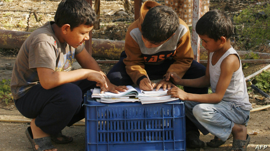 أطفال لاجئون أثناء حل واجبات مدرسية/ مصدر الصورة: ا ف ب
