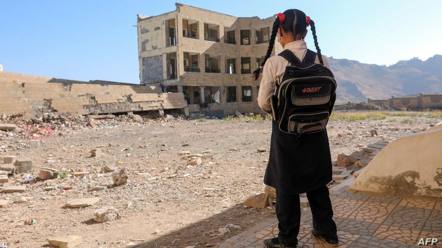 طفلة يمنية تقف أمام مدرستها المدمرة في مدينة تعز - أرشيف