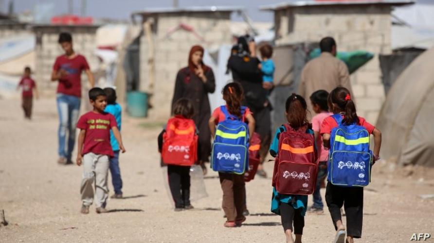 طلاب عراقيون يستعدون للذهاب إلى مدرسة في مخيم للاجئين/وكالة الصحافة الفرنسية