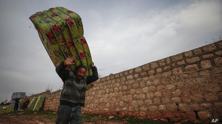 سوري يحمل أفرشة تلقاها كمساعدات إنسانية من الهلال الأحمر