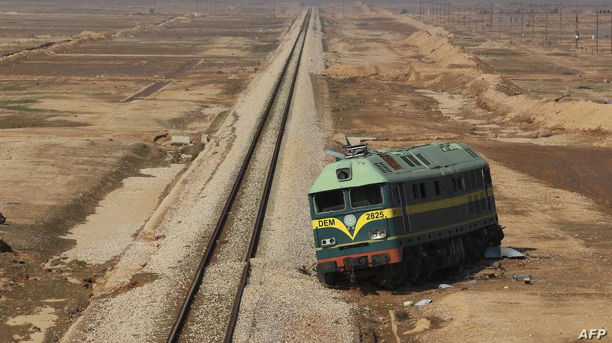 عربة قطار مهجورة على جانب السكة في صحراء الأنبار، بعدما تعرض القطار لهجوم شنه داعش.
