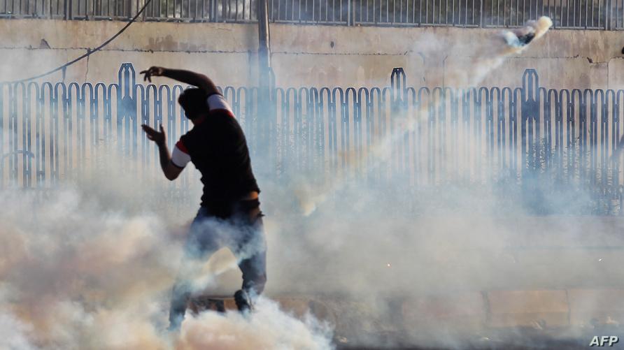 متظاهر عراقي يلقي بعيدا بقنبلة مسيلة للدموع خلال التظاهرات الاخيرة