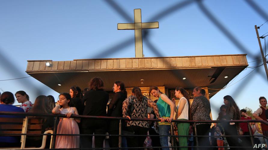 مسيحيون عراقيون يحضرون قداس أم مريم المقدسة في كنيسة مارم شموني في أربيل/وكالة الصحافة الفرنسية