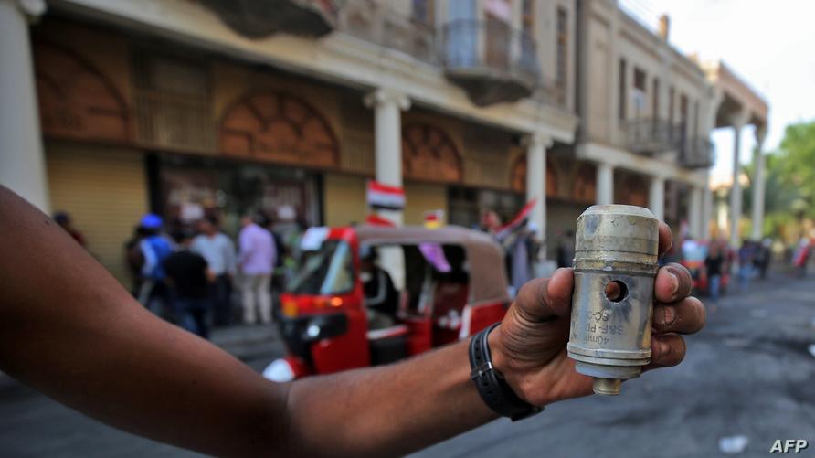 متظاهر يحمل عبوة فارغة من الغاز المسيل للدموع