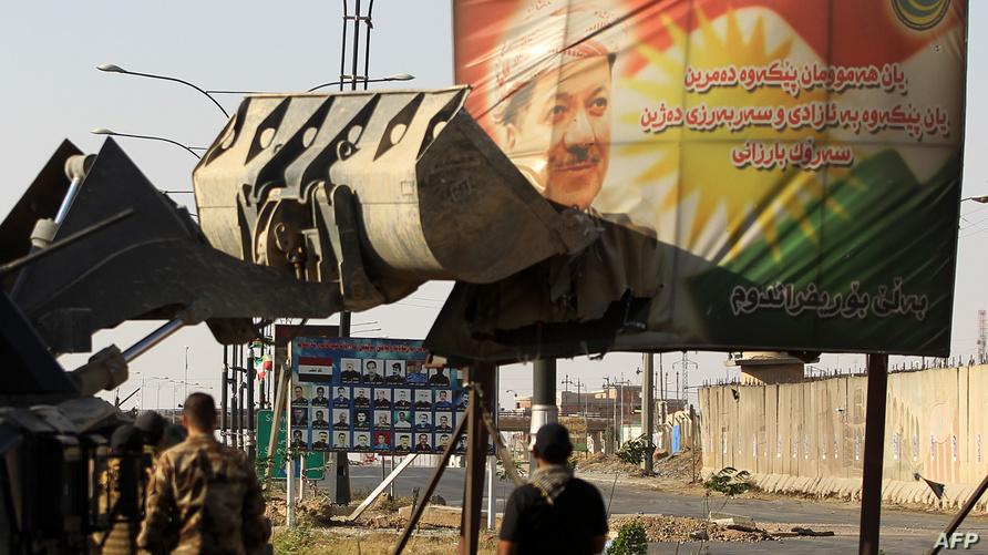إحدى آليات القوات العراقية اتزيل ملصقا لرئيس الإقليم مسعود برزاني جنوب كركوك/وكالة الصحافة الفرنسية