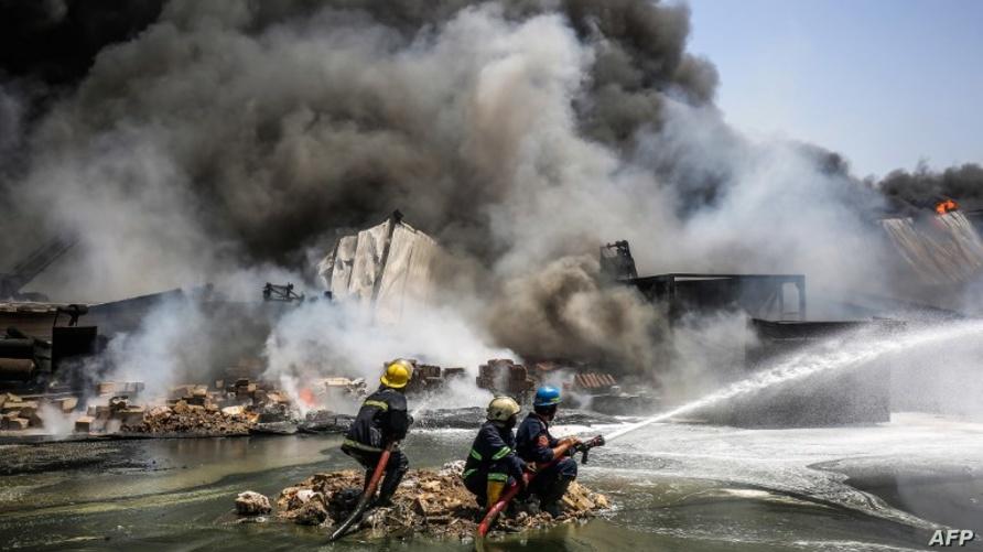 رجال إطفاء يحاولون إخماد حريق اندلع في مخزن في بغداد/وكالة الصحافة الفرنسية
