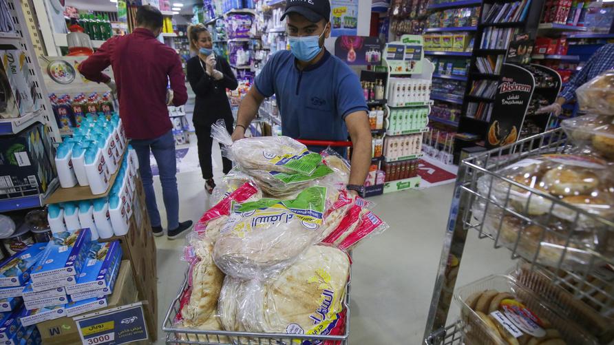 عامل يرتدي كمامة يدفع عربة محملة بالخبز في محل بيع مواد غذائية ببغداد