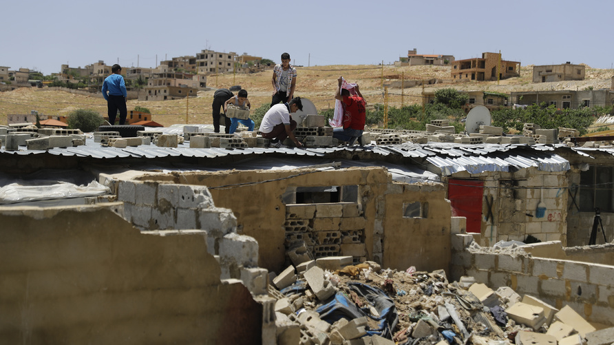 Syrian youths remove the roof of a refugee housing block as workers demolished concrete shelters at a refugee camp in the…