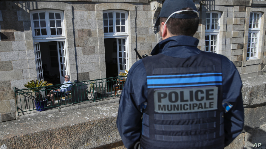 A man reads a book on his sunny terrace's apartment as French police patrol the streets of Saint-Malo, western France, Friday,…