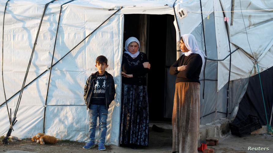 نساء أيزيديات وطفل يقفون عند مدخل خيمتهم في مخيم للاجئين بجبل سنجار شمال العراق
