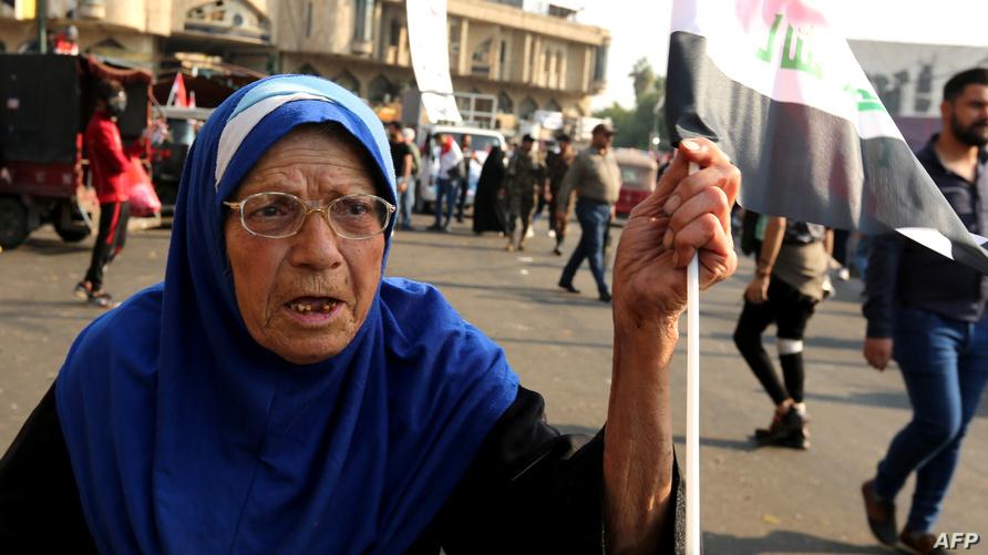 سيدة عراقية تشارك في التظاهرات في ساحة التحرير ملوحة بالعلم العراقي