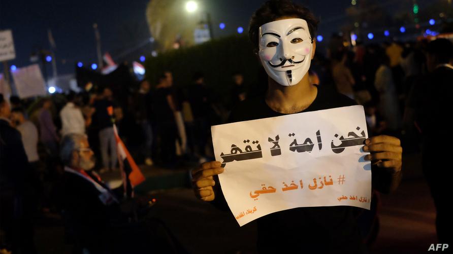"""متظاهر عراقي في كربلاء (نوفمبر) يرتدي قناع شخصية فيلم """"V For Vendetta"""" / ا ف ب"""