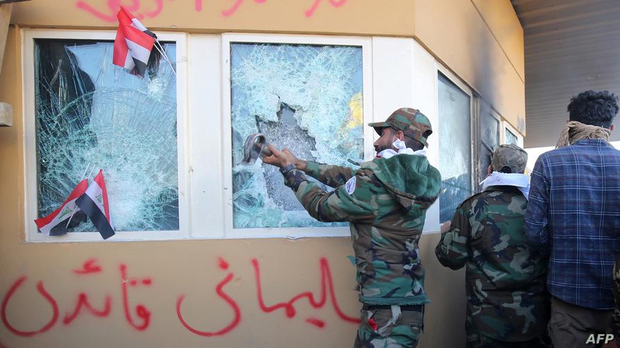 عنصر في الميليشيا العراقية يحاول تحطيم زجاج واجهة السفارة الأميركية في بغداد